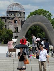 People gather to pray at the memorial for victims of the Hiroshima bombing at the Peace Memorial Park in Hiroshima, Japan