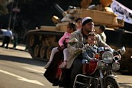 "An Egyptian family rides a motorbike past a tank outside the presidential palace in Cairo. Egypt's powerful military has demanded the Islamist-led government and political foes start dialogue and warned it will not permit events to take a ""disastrous"" turn"