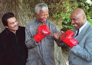 Nelson Mandela pretends to fight former US world middleweight champion Marvin Hagler (right) at his residence in Cape Town on November 12, 1997