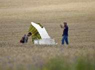 Malaysian air crash investigators take pictures of wreckage at the crash site of Malaysia Airlines Flight 17 near the village of Hrabove, eastern Ukraine, Tuesday, July 22, 2014. A team of Malaysian investigators visited the site along with members of the OSCE mission in Ukraine for the first time since the air crash last week. (AP Photo/Vadim Ghirda)