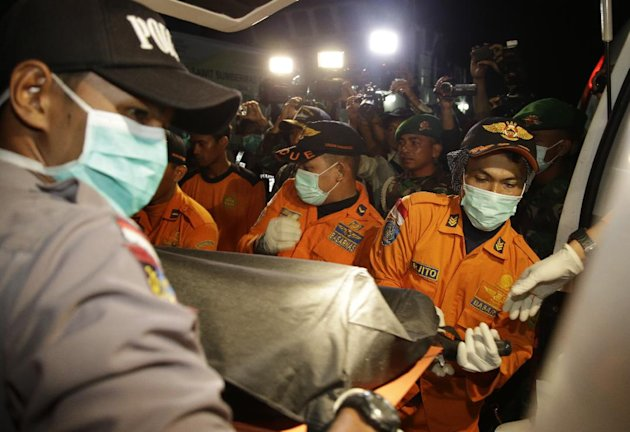 Officers of the National Search And Rescue Agency (BASARNAS) carry a victim's body of AirAsia flight QZ 8501 from a boat to an ambulance at Kumai port in Pangkalan Bun, Indonesia, Wednesday, Dec. 31, 2014. A massive hunt for the victims of the jet resumed in the Java Sea on Wednesday, but wind, strong currents and high surf hampered recovery efforts as distraught family members anxiously waited to identify their loved ones. (AP Photo/Achmad Ibrahim)