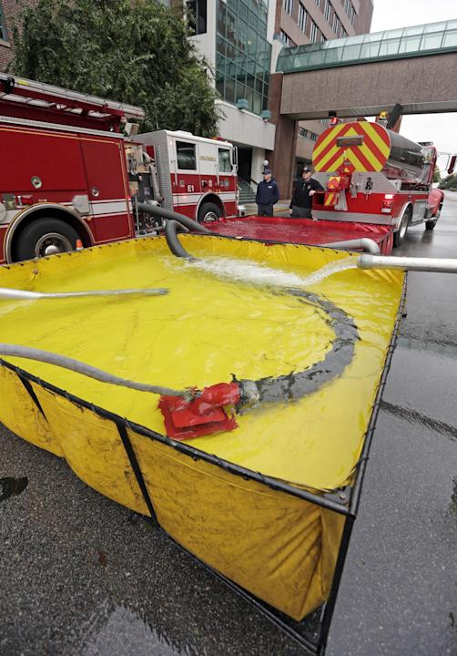 Firefighters use tanker trucks to pump water into Palmetto Health Baptist Hospital in Columbia, S.C., Monday, Oct. 5, 2015. A large part of the city is without water due to flooding from the east coas