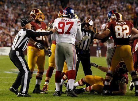 Referees and Redskins players intervene after Giants defensive tackle Joseph stomped on Redskins center Montgomery in Landover