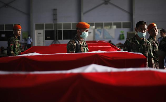 Indonesian soldiers stand among the coffins of the victims of a military plane that crashed on Tuesday, at Suwondo Airbase in Medan, North Sumatra, Indonesia, Friday, July 3, 2015. The aging C-130 Her
