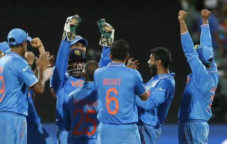 Members of India's cricket team celebrate after an electronic review gave them the wicket of Pakistan's batsman Umar Akmal during their Cricket World Cup match in Adelaide