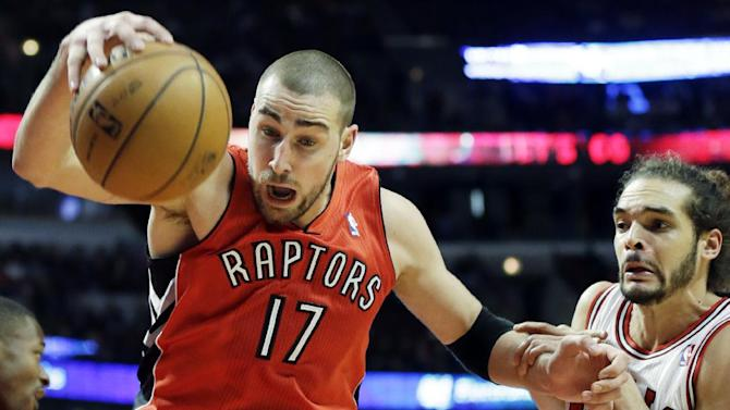 Toronto Raptors center Jonas Valanciunas, left, of Lithuania, rebounds the ball against Chicago Bulls center Joakim Noah during the second half of an NBA basketball game in Chicago on Saturday, Dec. 14, 2013. The Raptors won 99-77