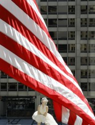 An American flag flying off the Wrigley Building is seen with Seward Johnson's 26-foot-tall sculpture of Marilyn Monroe, in her most famous wind-blown pose, across the street on Michigan Ave. Friday, July 15, 2011 in Chicago. (AP Photo/Charles Rex Arbogast)