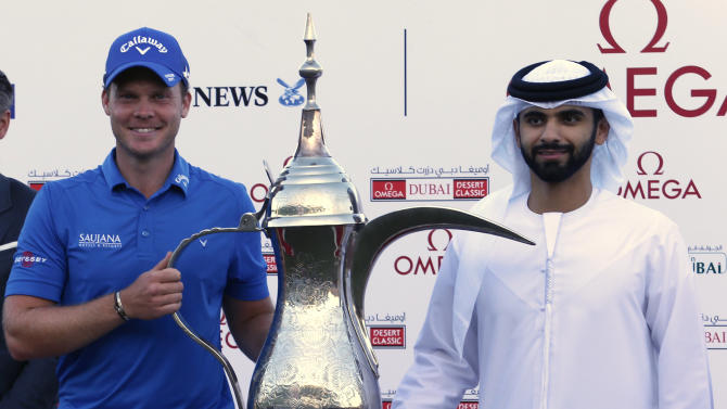 Willett of England poses with Sheikh Mansour bin Mohammed bin Rashid al-Maktoum after winning the Dubai Desert Classic golf championship in Dubai
