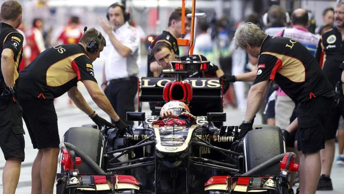 Lotus F1 Formula One driver Grosjean removes his gloves as he sits in his car during the third practice session of the Singapore F1 Grand Prix in Singapore
