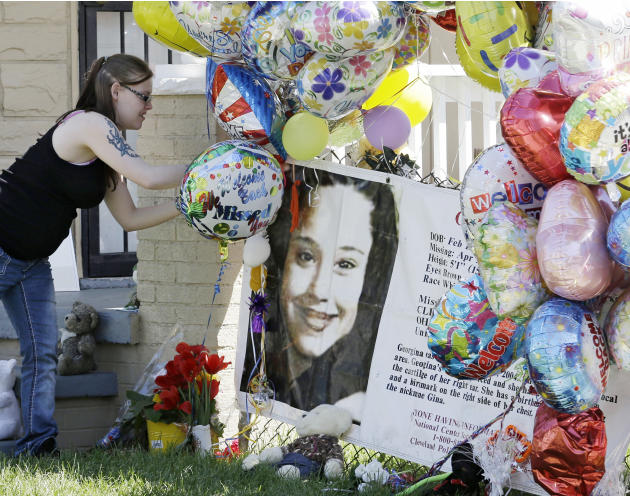 A girl adds a balloon outside the home of Gina DeJesus Thursday, May 9, 2013, in Cleveland. Ariel Castro, the man accused of raping and kidnapping DeJesus and 2 other women, who were missing for about