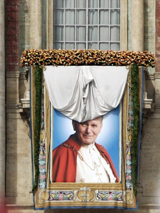 A giant tapestry of late Pope John Paul II is unveiled on the facade of St. Peter's basilica at the Vatican, Sunday, May 1, 2011. Pope Benedict XVI beatified Pope John Paul II before more than a milli