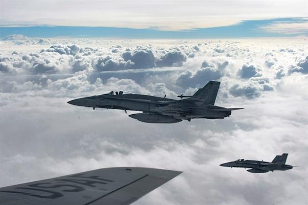 Royal Canadian Air Force CF-18 Hornets depart after refueling with a KC-135 Stratotanker assigned to the 340th Expeditionary Air Refueling Squadron, Thursday,  Oct. 30, 2014, over Iraq. Two Canadian fighter jets spent New Year's Eve bombing militants' positions in Iraq as part of a international airstrike campaign. THE CANADIAN PRESS/HO-U.S. Air Force Photo by Staff Sgt. Perry Aston