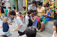 Children gather around a basketball court to play in Manila on January 3, 2013. A Catholic couple has asked the Philippines' top court to stop a historic birth control law, their lawyer said, in the first of many legal challenges church leaders have vowed against the measure