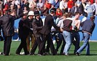 File photo shows policemen rescuing soccer fans at Hillsborough stadium on April 15, 1989, when 96 fans were crushed to death and hundreds injured after support railings collapsed during a match between Liverpool and Nottingham Forest.