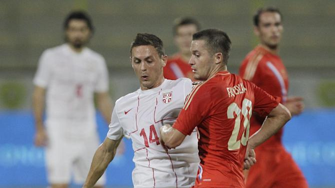 Serbia's Nemanja Matic, left, fights for the ball with Russia's Victor Fayzolin during a friendly match Dubai, United Arab Emirates, Friday Nov. 15, 2013