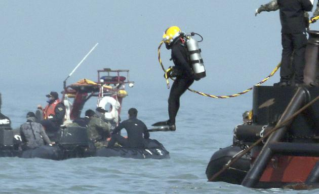 A diver jumps into the sea near an area where the capsized passenger ship Sewol sank during a rescue operation in Jindo