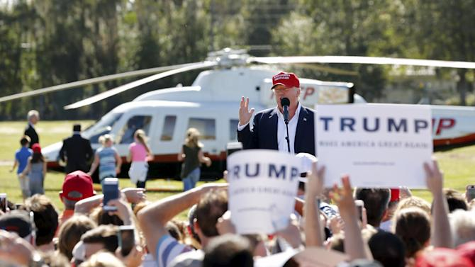U.S. Republican presidential candidate Donald Trump speaks after arriving in his helicopter as a group of children race towards it for ride during a rally in Sarasota, Florida