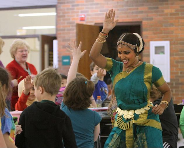 Shandha Mair of Chicago high fives students after dancing a classical Indian dance called Bharatanatyam as Butterfield School had their last Arts As We Lunch program Friday in Libertyville, IL on Frid