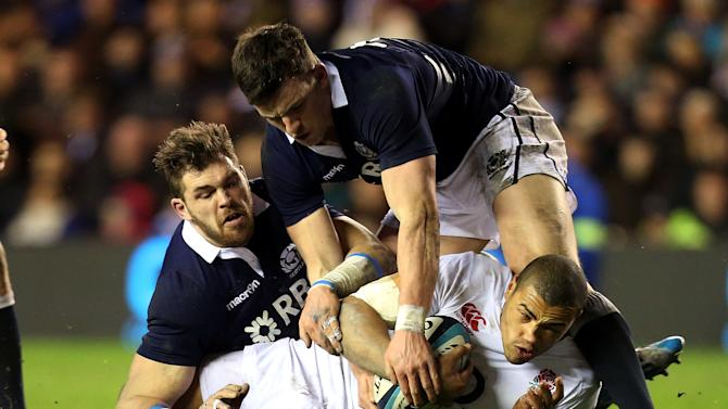 England's Luther Burrell, bottom, is tackled by Scotland's Matthew Scott, top, and Sean Lamont, left, during their Six Nations rugby union international match at Murrayfield, Edinburgh, Scotland, Saturday Feb. 8, 2014. (AP Photo/Scott Heppell)