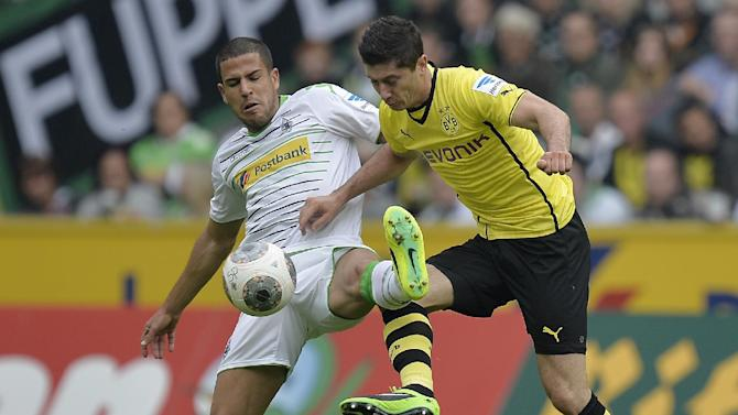 Moenchengladbach's Alvaro Dominguez of Spain, left, and Dortmund's Robert Lewandowski of Poland challenge for the ball during the German first division Bundesliga soccer match between Borussia Moenchengladbach and Borussia Dortmund in Moenchengladbach, Germany, Saturday, Oct. 5, 2013