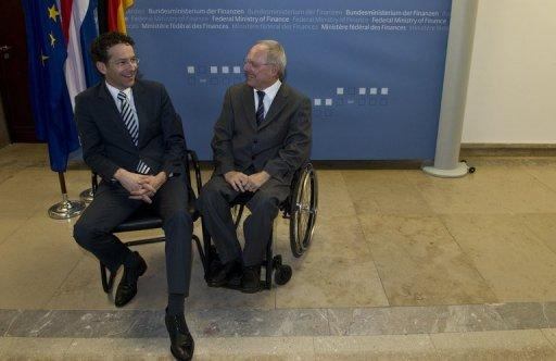 "German Finance Minister Wolfgang Schaeuble (right) chats with his Dutch counterpart Jeroen Dijsselbloem in Berlin on December 17, 2012. Schaeuble warned Britain in a Sunday newspaper interview against ""blackmailing"" its EU partners in a bid to bring powers back home from Brussels."