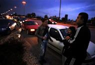 People stand next to their cars, parked on the Sofia ring road after a strong quake, in the Bulgarian capital early on May 22, 2012. The 5.8-magnitude quake rocked Bulgaria shortly after 3:00 am (0000 GMT)