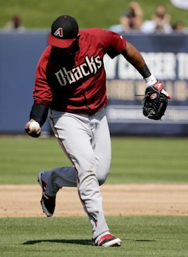 Yasmany Tomas one hands a ball hit by Brewers' Jean Segura during a spring training game. (AP)