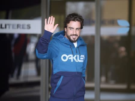 McLaren's Formula One driver Alonso of Spain gestures to the media as he leaves a hospital where he has been hospitalized since Sunday, in Sant Cugat