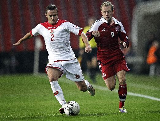 Malta's Alex Muscat, left, and Denmark's Michael Krohn-Dehli challenge for the ball during their  Group B 2014 FIFA World Cup qualifying soccer match played in Parken, Copenhagen on Tuesday, Oct 15, 2013