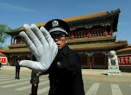 A Chinese policeman blocks photos being taken outside Zhongnanhai which serves as the central headquarters for the Communist Party of China in Beijing in April 2012. China's decision to try fallen politician Bo Xilai's wife for murder underscores Communist leaders' determination to draw a line under a scandal that has engulfed the party ahead of a power handover, analysts say