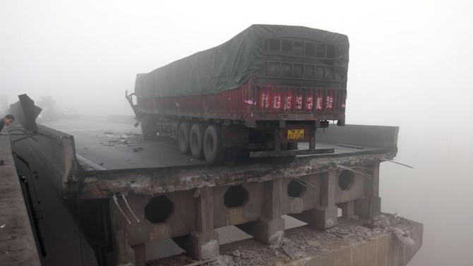 In this photo provided by China's Xinhua News Agency, a truck sits on the expressway bridge which partially collapsed due to an explosion in Mianchi County, Sanmenxia, central China's Henan Province, Thursday, Feb. 1, 2013.  Fireworks for Lunar New Year celebrations exploded on a truck in central China, destroying part of an elevated highway Friday and sending vehicles plummeting 30 meters (about 100 feet) to the ground. (AP Photo/Xinhua, Xiao Meng)