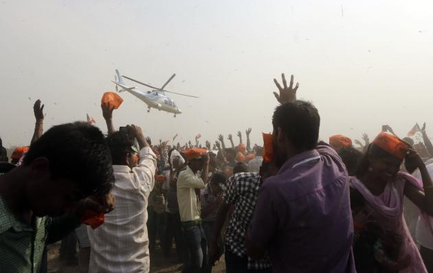 Supporters of India's main opposition Bharatiya Janata Party (BJP) wave towards a chopper carrying their prime ministerial candidate Narendra Modi as he leaves after an election campaign rally in