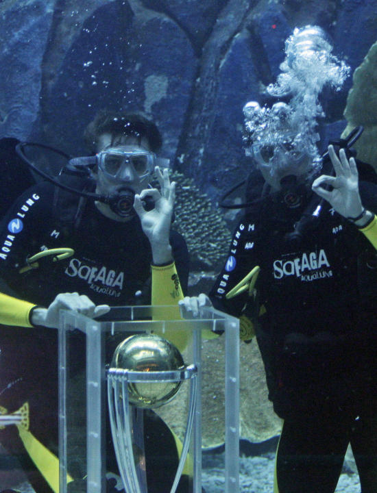 South African cricket players, Morne Morkel, left, and Dale Steyn pose with the ICC Cricket World Cup Trophy in the Dubai Aquarium & Under Water Zoo to mark the 100-day countdown to the opening ceremo