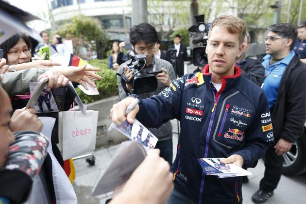 Red Bull Formula One driver Sebastian Vettel of Germany signs autographs to fans ahead of the Chinese F1 Grand Prix in Shanghai