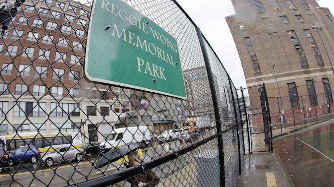 In this Nov. 29, 2016 photo, a woman walks by Reggie Wong Park on a rainy day. The fate of the modest asphalt court near where Boston Chinatown immigrants created a unique style of volleyball is uncertain. The state is seeking proposals to develop the prime slice of real estate south of downtown that's home to Reggie Wong Park, a steam plant and a state government office. The park is the latest battleground in the long-simmering debate over gentrification in one of the nation's oldest and largest Chinatowns. (AP Photo/Elise Amendola)