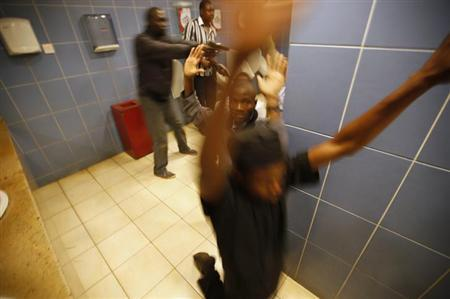 Armed police search customers taking cover inside a bathroom while combing through the Westgate shopping centre for gunmen in Nairobi, September 21, 2013. Gunmen stormed a shopping mall in the Kenyan capital on Saturday killing at least 15 people, according to the Kenyan Red Cross, and sending scores fleeing into shops, a cinema and onto the streets seeking safety. REUTERS/Goran Tomasevic