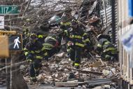 New York City Firefighters dig through rubble at an apparent building explosion fire and collapse in the Harlem section of New York, March 12, 2014. Two women were killed in the building collapse in Upper Manhattan on Wednesday, New York City Police said. REUTERS/Brendan McDermid (UNITED STATES - Tags: DISASTER)