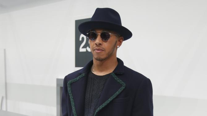 British Formula One motor racing driver Lewis Hamilton poses before the Spring/Summer 2016 women's ready-to-wear collection for fashion house Chanel in Paris