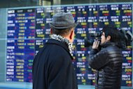 People pass an electronic share price board in Tokyo. Asian markets climbed on Thursday after China released better-than-expected trade data that provide further evidence the world's number two economy has emerged from a drawn-out slumber