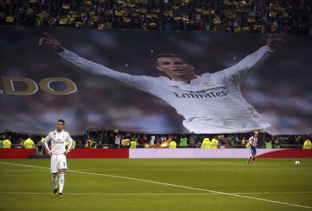 Real Madrid's Cristiano Ronaldo walks on the pitch in front of a banner of himself prior to their King's Cup round of 16 second leg soccer match in Madrid