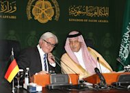 Saudi Foreign Minister Prince Saud al-Faisal (R) and German Foreign Minister Frank-Walter Steinmeier speak to each other during a press conference following their meeting in the coastal City of Jeddah, on October 13, 2014.
