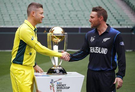 Australia's captain Michael Clarke shakes hands with New Zealand captain Brendon McCullum as they stand next to the Cricket World Cup trophy ahead of their final match at the MCG