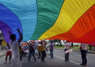 Participants raise a giant gay pride flag during the annual Pride March in Manila, Philippines, Saturday, Dec. 3, 2011. Lesbians, gays, bisexual and transgenders called for the urgent need to pass the anti-discrimination bill and for government protection from hate crimes committed against them. (AP Photo/Pat Roque)