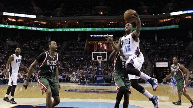 Charlotte Bobcats' Kemba Walker (15) drives past Milwaukee Bucks' Khris Middleton (22) as John Henson (31) looks on during the second half of an NBA basketball game in Charlotte, N.C., Monday, Dec. 23, 2013. The Bobcats won 111-110 in overtime