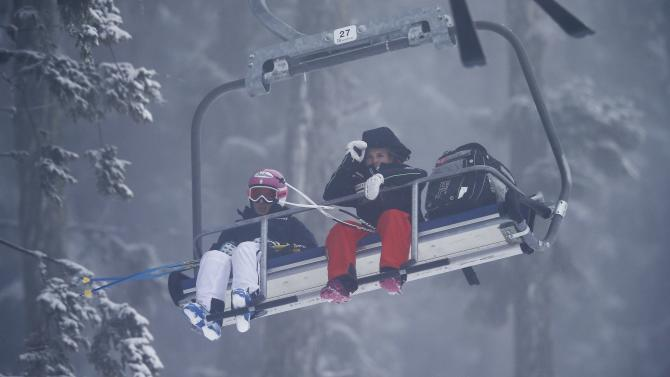Fanchini of Italy and Gut of Switzerland use a ski lift after the women's Super G event of the Alpine Skiing World Cup was cancelled due to fog in Bansko