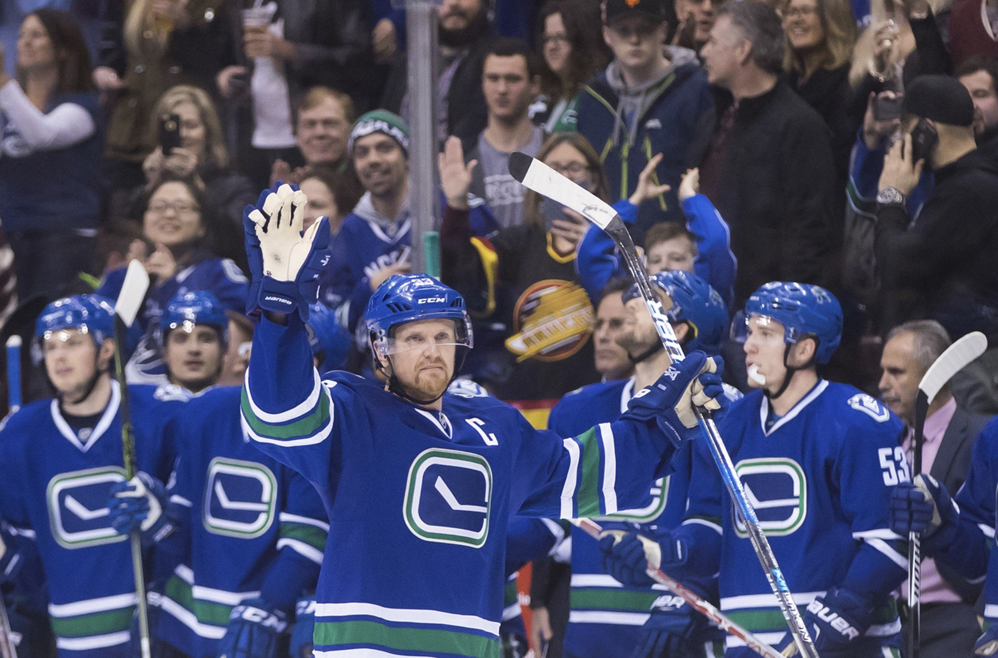 Vancouver Canucks' Henrik Sedin, of Sweden, waves as he receives a standing ovation from his teammates on the bench and the crowd after scoring a goal against the Florida Panthers to record his 1,000th career point, during the second period of an NHL hockey game Friday, Jan. 20, 2017, in Vancouver, British Columbia. (Darryl Dyck/The Canadian Press via AP)