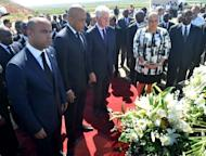 From L to R, Haitian Prime Minister Laurent Lamorthe, Haitian President Michel Martelly, UN special envoy to Haiti former US president Bill Clinton and Haitian First Lady Sophia Martelly observe a minute of silence on January 12, 2013 in Titanyin, 14km from Port-au-Prince, at a communal grave for a memorial ceremony in honor of the victims of the January 12, 2010 earthquake in Haiti