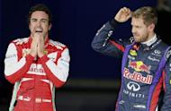 Red Bull Formula One driver Sebastian Vettel (R) of Germany and Ferrari Formula One driver Fernando Alonso of Spain react after Vettel took pole position at the qualifying session of the Brazilian F1 Grand Prix at the Interlagos circuit in Sao Paulo November 23, 2013. REUTERS/Paulo Whitaker