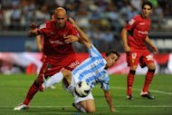 Mallorca's Jose Nunes (L) and Malaga's Sebastian Fernandez (C) during their Spanish League match on August 25. Before the break, Fernandez hit straight at Mallorca keeper Dudu Aouate and after the restart the game became more scrappy as Malaga appeared to run out of ideas