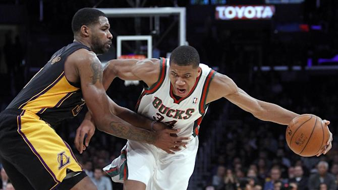 Milwaukee Bucks shooting guard Giannis Antetokounmpo, right, drives against Los Angeles Lakers forward Shawne Williams during the second half of an NBA basketball game Tuesday, Dec. 31, 2013, in Los Angeles. The Bucks won 94-79